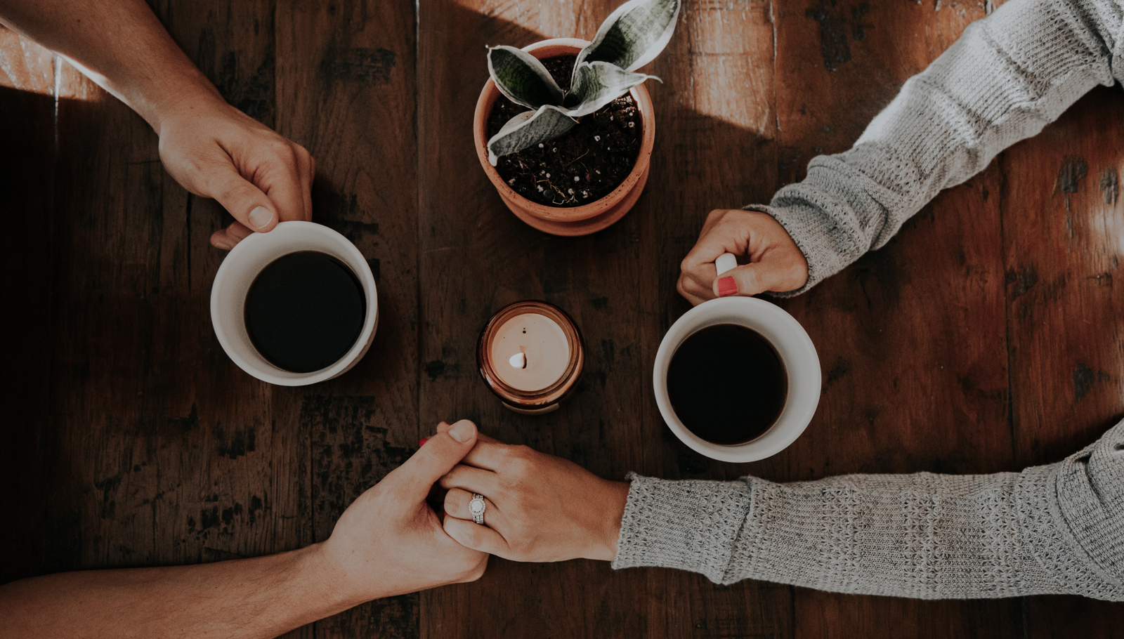 table top with couple holding hands drinking coffee