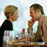Couple sitting face-to-face at restaurant table, smiling